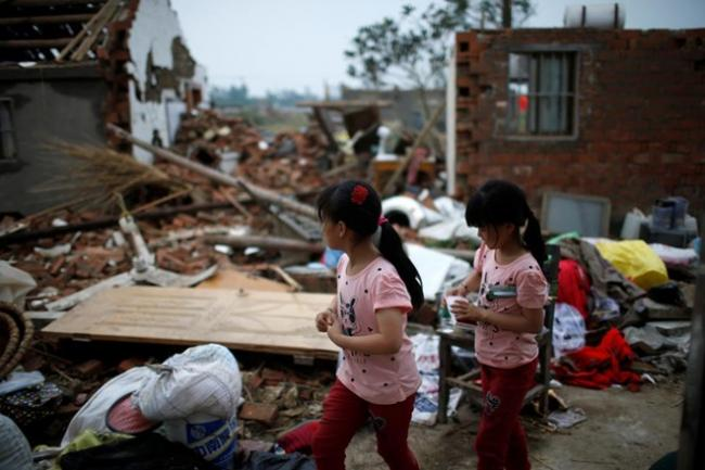 Children picking up their belongings from their home after it was ravaged by a tornado. - Sakshi Post