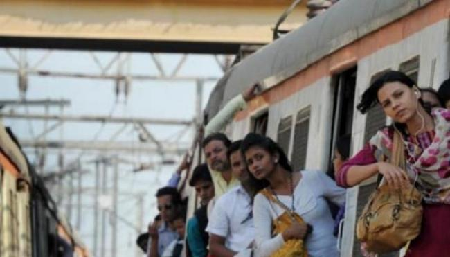 Woman passengers hanging from a moving train. - Sakshi Post