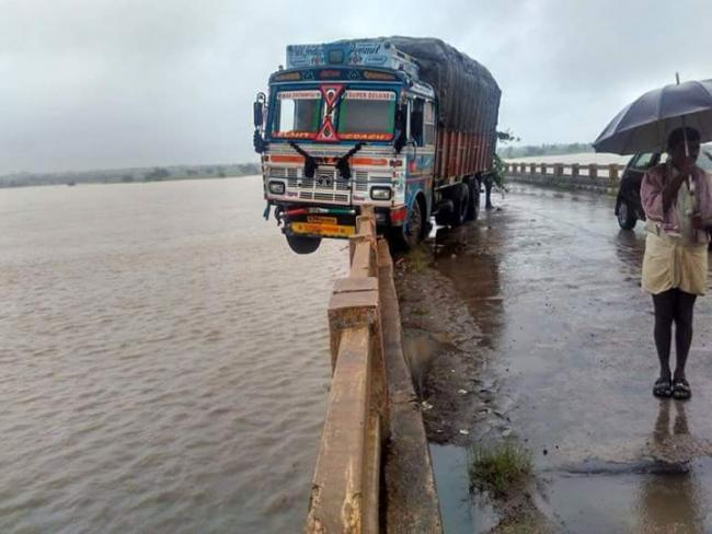 Both driver and his assistant were forced to stay put inside the cabin all the night as they feared of the truck falling down into the river - Sakshi Post