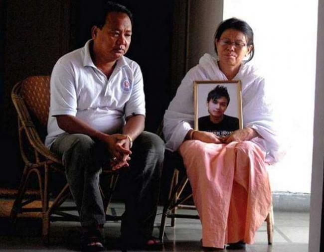 Irom Roger's parents with his potrait. - Sakshi Post