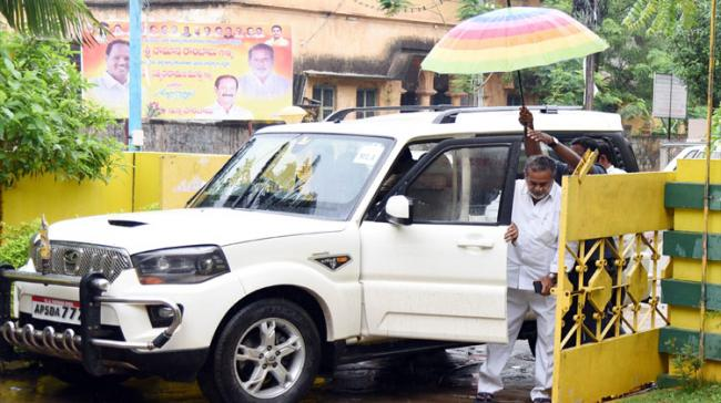 Pilli Sattibabu getting down from the car and the security guard holding an umbrella - Sakshi Post