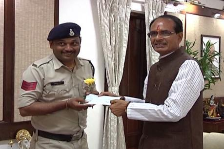 Chief minister Shivraj Singh Chouhan handing over a cheque to head constable Abhishek Patel for his exceptional bravery in saving the lives of school children. - Sakshi Post