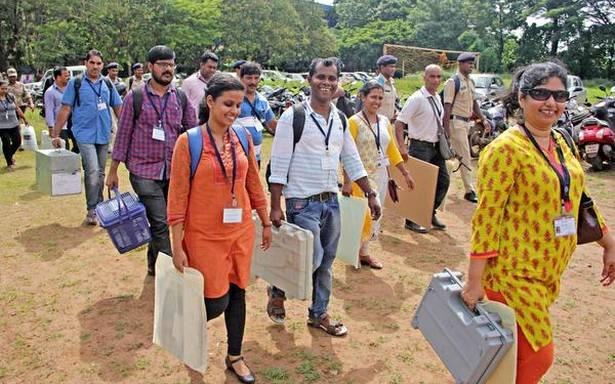 Polling officials carry voting machines to their designated polling booths prior to the bypolls in Goa. - Sakshi Post