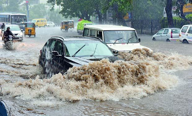 Vehicles  struggling through a flooded street in Hyderabad on Monday evening. - Sakshi Post