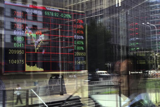 People and office buildings are reflected on a brokerage houses window as an electronic board displaying stock trading index  - Sakshi Post