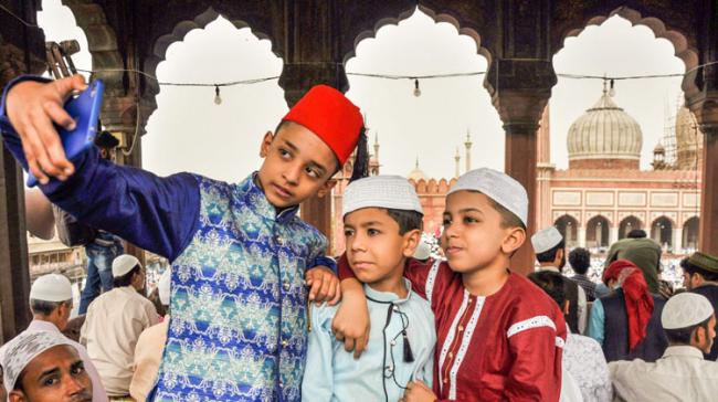 Muslim children pose for a selfie after offering namaz on the occasion of Eid-ul-Fitr at Jama Masjid, in New Delhi  - Sakshi Post
