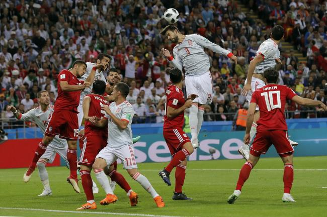 Spains Gerard Pique, center, jumps for a header during the group B match between Iran and Spain at the 2018 soccer World Cup in the Kazan Arena in Kazan, Russia, Wednesday, June 20, 2018.  - Sakshi Post
