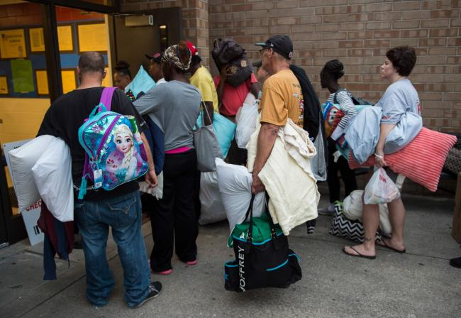 People line up to enter a hurricane shelter at Trask Middle School in wilmington, North Carolina. - Sakshi Post