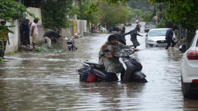 A woman trying to move her scooty in a waterlogged street - Sakshi Post