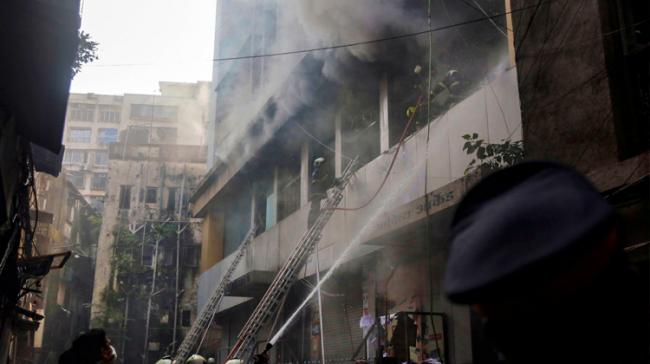 Fire personnel douse a fire which broke out in a commercial building in Mumbai, Sunday   - Sakshi Post