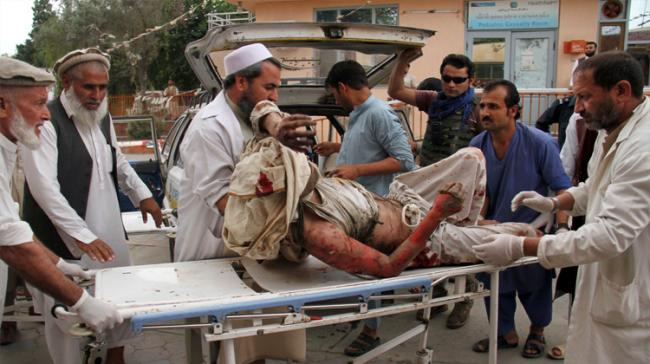 A wounded man is brought by stretcher into a hospital after a mortar was fired by insurgents in Haskamena district of Jalalabad east of Kabul, Afghanistan - Sakshi Post