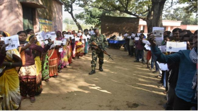 A security man guarding the polling booth while during election in Jharkhand - Sakshi Post
