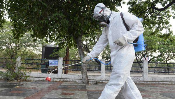<a>A member from Disaster Response Force (DRF) of Telangana State, wearing a protective gear sprays disinfectant on a pedestrian footpath </a> - Sakshi Post
